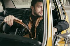Pensive handsome stylish man sitting in retro car and looking. Away royalty free stock images