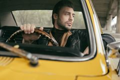 Pensive handsome stylish man sitting in vintage car and looking. Away stock image