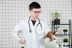 Pensive handsome young male doctor using tablet computer. Technologies in medicine concept stock photography