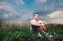 Pensive handsome young man sitting on on the green grass on a ba Royalty Free Stock Images