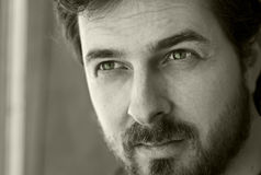 Pensive handsome young masculine man. Black and white portrait of a masculine bearded guy royalty free stock photo