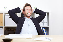 Pensive happy business man. In office relaxing with hands behind his head stock image