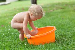 Pensive happy cute curly baby is bathed in orange pelvis Royalty Free Stock Images