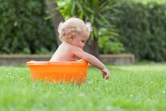 Pensive happy cute curly baby is bathed in orange pelvis Stock Photo