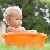 Pensive happy cute curly baby is bathed in orange pelvis Royalty Free Stock Photos
