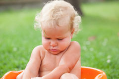 Pensive happy cute curly baby is bathed in orange pelvis Royalty Free Stock Photography