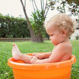 Pensive happy cute curly baby is bathed in orange pelvis Stock Photos