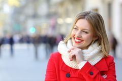 Pensive happy woman looking at side in winter in the street. Pensive happy woman in red looking at side in winter standing in the street royalty free stock image