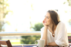 Pensive happy woman remembering. Looking at side sitting in a bar or home terrace Royalty Free Stock Photos