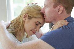 Couple in love spending time together. Pensive happy young men cuddling with girlfriend and smelling her hair stock image
