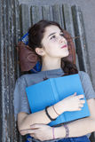 Pensive hipster girl lying on bench with blue book, adolescence lifestyl Royalty Free Stock Photo