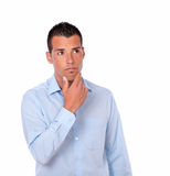 Pensive hispanic man looking at people. Portrait of a pensive hispanic man on blue stylish shirt looking at people on isolated background - copyspace royalty free stock photo