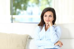 Pensive homeowner sitting on a couch at home royalty free stock photography