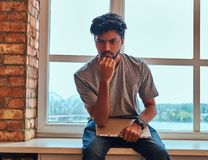 Pensive indian student holds the laptop while sitting on a window sill in a student dormitory. Pensive indian student holds the laptop while sitting on a window royalty free stock photography