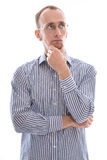 Pensive isolated young man in a blue shirt and glasses Royalty Free Stock Image