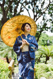 Pensive Japanese woman. In traditional clothes walking around the garden Stock Photos
