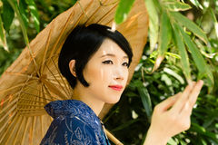 Pensive Japanese woman with umbrella. Portrait of pensive Japanese woman with traditional umbrella Royalty Free Stock Image