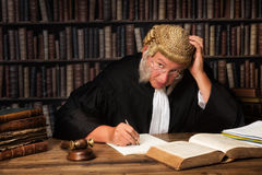 Pensive judge. Mature judge with authentic court wig and gavel in court stock photography