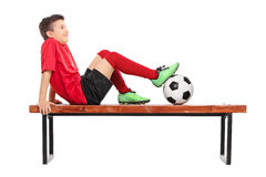 Pensive junior football player sitting on a bench Royalty Free Stock Image