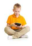 Pensive kid boy sitting with tablet pc or phablet isolated Stock Images