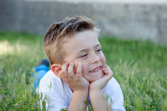 Pensive kid lying on the grass Stock Photo