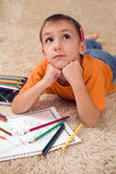 Pensive kid with pencils on the carpet Royalty Free Stock Photos