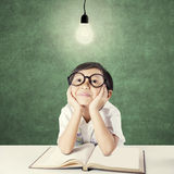 Pensive kid with textbook sitting under lightbulb Royalty Free Stock Image