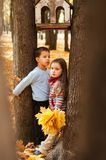 Pensive kids stand between two trees Royalty Free Stock Photo