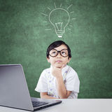 Pensive kindergarten student with laptop Royalty Free Stock Images