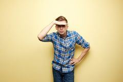 Pensive l guy dressed in a plaid shirt and jeans stands next to yellow wall in the studio and looking for something stock photos