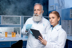 Pensive laboratory technicians in lab coats looking at camera. At laboratory stock photo