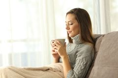 Pensive lady holding a cup of coffee at home in winter. Pensive lady holding a cup of coffee in winter sitting on a couch in the living room at home stock image