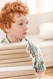 Pensive little boy holding pile of books Royalty Free Stock Image