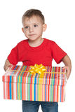Pensive little boy holds a gift box Royalty Free Stock Photography