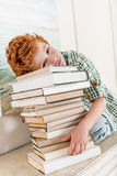 Pensive little boy leaning on pile on books Stock Photography