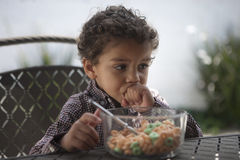 Pensive little boy looking away with cereal bowl on table royalty free stock photos