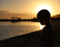 Pensive little boy by the sea. Little boy's silhouette on the beach at sunset Stock Photos