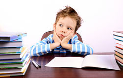 Pensive little boy sitting at a desk. On the table are many books and a notebook. ruffled the boy's hair. he holds his head. on a light background. horizontal Stock Photography