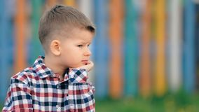 Pensive little boy sitting outside on a colourful background.  stock video footage