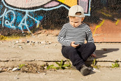 Pensive little boy sitting thinking Stock Image