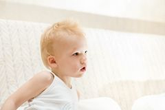 Pensive little boy sitting on white sofa Stock Images