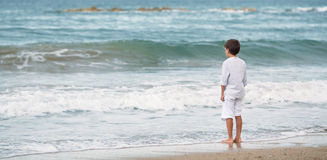 Pensive little boy standing on the beach, meditation Royalty Free Stock Photography