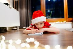 Pensive little boy writing a letter to Santa Claus Royalty Free Stock Photography