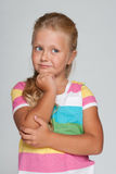 Pensive little girl on the gray background Royalty Free Stock Image