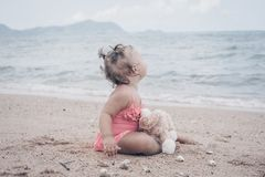 Pensive little girl hugging teddy bear and looking away while sitting on seashore. royalty free stock image