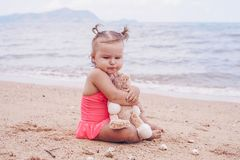 Pensive little girl hugging teddy bear and looking away while sitting on seashore. stock photos