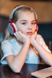 Pensive little girl listening music in headphones Stock Photo