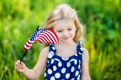 Pensive little girl with long blond hair holding american flag. Pretty pensive little girl with long curly blond hair holding an american flag and smiling on royalty free stock photography