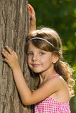 Pensive little girl near a tree Royalty Free Stock Photos
