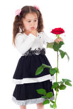 Pensive little girl with red rose Royalty Free Stock Image